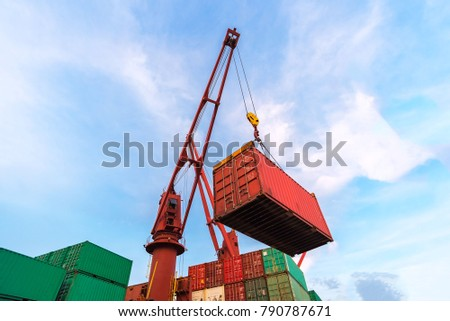 Industrial crane loading Containers in a Cargo freight ship,Container Cargo freight ship by crane bridge, logistics harbor at sunrise