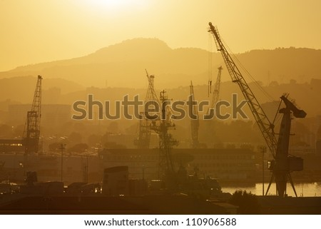 industrial cranes in Toulon port at sunset, France