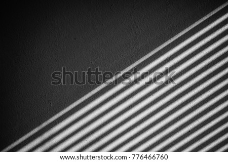 Industrial design window sunlight parallel lines shadows. Light and shadow from the window. Thin lines of light on the wall. The texture of the plaster. Shadow from the blinds. Place for your text.