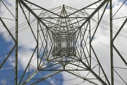 Industrial electrical transmission lines and pylon tower. Repeating, converging and intricate patterns are created by the metal lattice structure.
