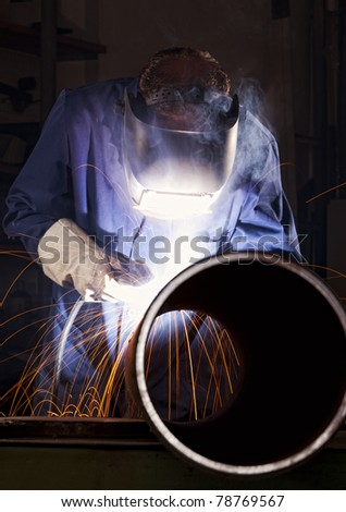 Industrial electrode welder with face shield and blue overall welding a steel pipe in workshop.