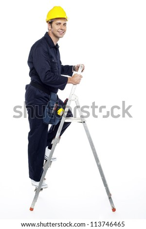 Industrial employee stepping up the ladder and looking at you