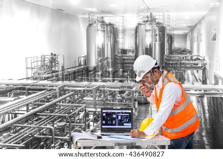 Industrial engineer checking machine status with laptop computer