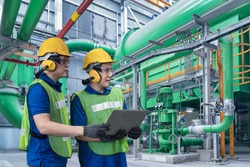 Industrial Engineer in Hard Hat Uses tablet while Standing in the Industry Manufacturing Factory. Oil and Gas Refinery Background. Two Factory worker in a hard hat on Heavy equipment and pipeline