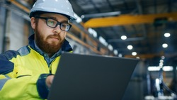 Industrial Engineer in Hard Hat Wearing Safety Jacket Uses Touchscreen Laptop. He Works at the Heavy Industry Manufacturing Factory. In the Background Welding/ Metalworking Processes are in Progress.