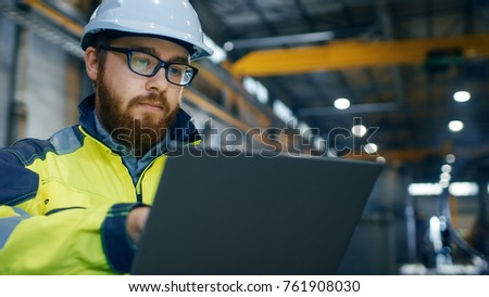 Industrial Engineer in Hard Hat Wearing Safety Jacket Uses Touchscreen Laptop. He Works at the Heavy Industry Manufacturing Factory. In the Background Welding/ Metalworking Processes are in Progress. #761908030