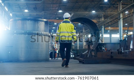 Industrial Engineer in Hard Hat Wearing Safety Jacket Walks Through Heavy Industry Manufacturing Factory with Various Metalworking Processes.