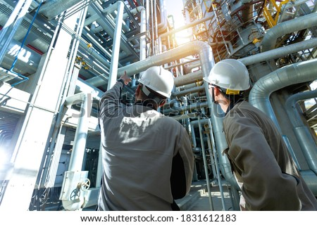 Industrial engineer or worker checking pipeline at oil and gas refinery plant form industry zone with sunrise and cloudy sky, oil and gas Industry concept.