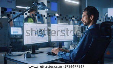 Industrial Engineer Solving Problems, Working on a Personal Computer, Two Monitor Screens Show CAD Software with 3D Prototype of Eco-Friendly Electric Engine Concept.
