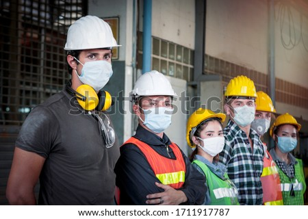 Industrial engineer worker women and men wearing helmet and mask in line waiting to work together at manufacturing plant factory, young people working in industry