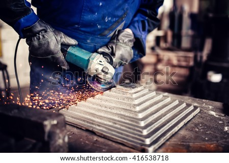 industrial engineer working on cutting a metal and steel bar with angle grinder, metallurgic factory details