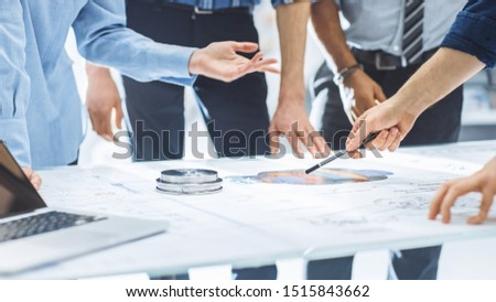 Industrial Engineering Facility: Close-up on Hands of Group of Engineers, Technicians and Specialists on a Meeting, Tracing Lines and Analysing Engine Design Technical Drafts Laying on the Table