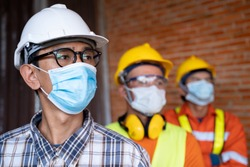Industrial engineering team wears a COVID 19 protective mask. Workers wear a quarantine mask to prevent the spread of Covid 19 by wearing a face mask. Coronavirus disease.