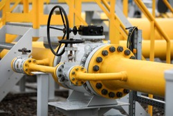 Industrial equipment (pipes, manometer/pressure gauge, levers, faucets, indicators) in a natural gas compressor station.