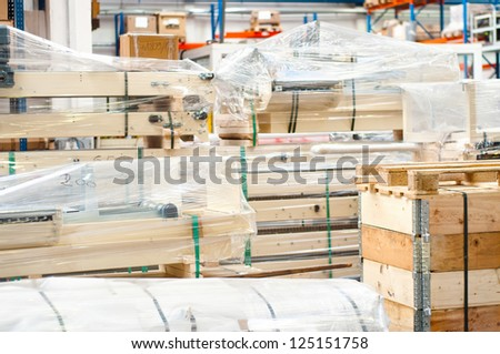 Industrial equipment stored in modern warehouse, on wooden pallets
