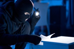 Industrial Espionage. Masked intruder holding and reading confidential documents using flashlight at night, copy space