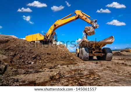 industrial excavator loading soil from sandpit into a dumper truck