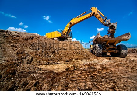 Industrial excavator loading soil material from highway construction site into a dumper truck