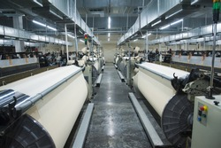 Industrial fabric production line. Weaving looms at a textile factory