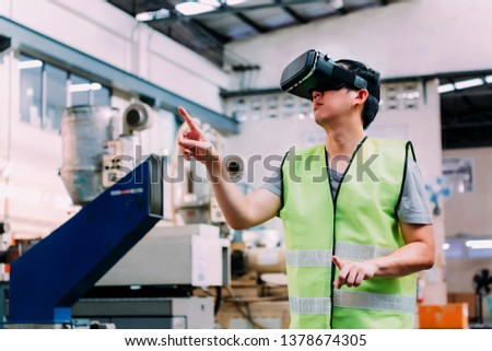 Industrial factory and manfacturing engieering worker wearing VR goggle headset touching in virtual reality simulation alongside heavy duty machines