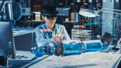 Industrial Factory Chief Engineer Wearing AR Headset Designs a Prototype of an Electric Motor on the Holographic Projection Blueprint. Futuristic Virtual Design of Mixed Technology Application.