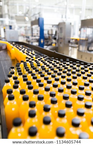 Industrial factory indoors and machinery. Robotic factory line for processing and bottling of soda and orange juice bottles. #1134605744