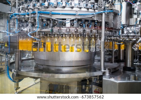 Industrial factory indoors and machinery. Robotic factory line for processing and bottling of soda and orange juice bottles. Selective focus. Short depth of field. #673857562