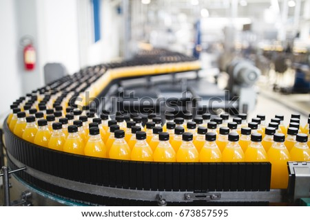 Industrial factory indoors and machinery. Robotic factory line for processing and bottling of soda and orange juice bottles. Selective focus. Short depth of field. #673857595