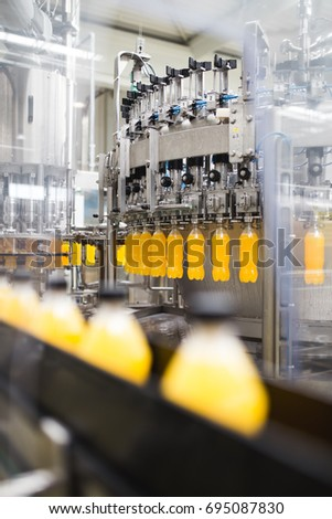 Industrial factory indoors and machinery. Robotic factory line for processing and bottling of soda and orange juice bottles. Selective focus. Short depth of field. #695087830