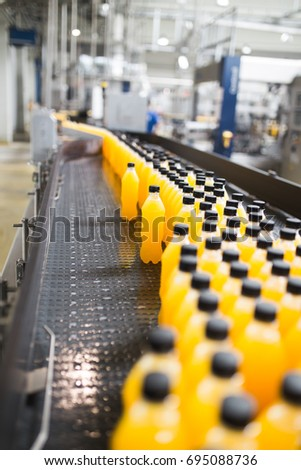 Industrial factory indoors and machinery. Robotic factory line for processing and bottling of soda and orange juice bottles. Selective focus. Short depth of field. #695088736