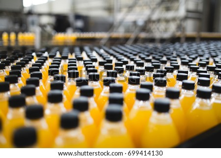 Industrial factory indoors and machinery. Robotic factory line for processing and bottling of soda and orange juice bottles. Selective focus. Short depth of field. #699414130