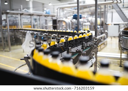 Industrial factory indoors and machinery. Robotic factory line for processing and bottling of soda and orange juice bottles. Selective focus. Short depth of field. #716203159