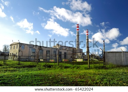 industrial factory producing electricity with pipes against blue sky