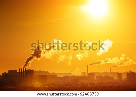 Industrial factory smoke from smokestacks over sunset sky