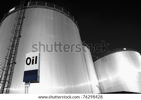industrial fuel and oil storage tanks, towers, large commercial oi-sign in foreground, silver duplex toning idea