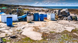 Industrial garbage such as plastic barrels, rusty fridges and pallet polluting the beautiful rocky coastal beach of the island of Inis Oirr, sunny day on the island of Inisheer, Ireland