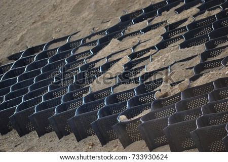 Industrial geocells in use some of them filled with sand and others empty. Geogrid, Driveway Grid, Ground Reinforcement Grids #733930624