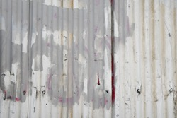 Industrial ghetto style abandoned corrugated metal fence texture with painted over graffiti