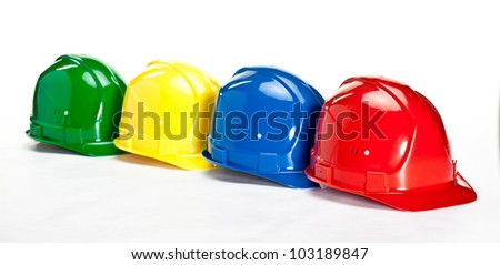 Industrial hardhats on white background; four multicolored construction hardhats