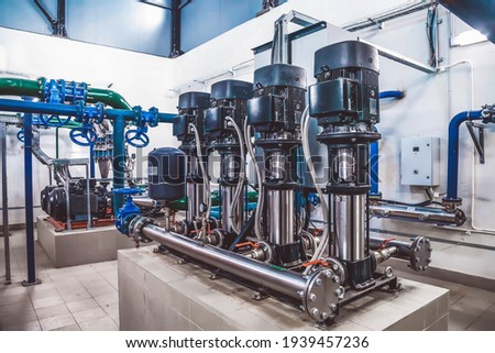 Industrial interior of water pump, valves, pressure gauges, motors inside engine room. Valve and pumps in an industrial room. Urban modern powerful pipelines and pumps, automatic control systems Foto stock ©