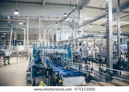 Industrial interiors. Robotic factory line for processing and quality control of pure spring water bottled into canisters. Low light and small amount of noise visible.