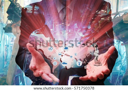 Industrial internet of things concept .Man hand holding cellphone with Infographic Industry4.0 icons screen and blue tone of automate wireless Robot arm in smart factory background