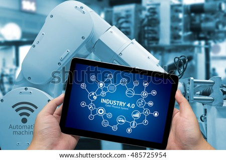 Industrial internet of things concept .Man hand holding tablet with Infographic Industry4.0 icons screen and blue tone of automate wireless Robot arm in smart factory background