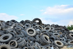 Industrial landfill for the processing of waste tires and rubber tyres. Pile of old tires and wheels for rubber recycling. Tyre dump