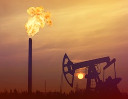 Industrial landscape. Gas torch on a background of sunset sky. Oil Field.