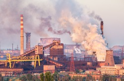 Industrial landscape in Ukraine. Steel factory at sunset. Pipes with smoke. Metallurgical plant. steelworks, iron works. Heavy industry in Europe. Air pollution from smokestacks, ecology problems.