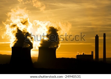industrial landscape of power station at sunset ommitting pollution into evening sky
