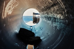 Industrial landscape, view of the sea and the end of the large tube from the inside of a scratched tube pipe