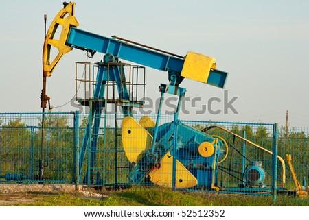Industrial landscape with an oil pump at sunset