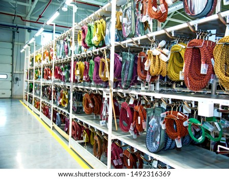 Industrial landscape with shelves of colored wire ropes at a modern plant for the production of wiring for automobiles. Logistics #1492316369